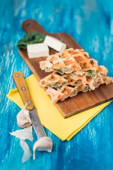 Vista elevada de waffles salados sobre tabla de madera con queso; cuchillo y dientes de ajo sobre fondo azul con textura