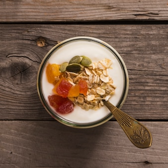 Vista elevada de yogur con muesli, semillas de calabaza y frutas en la rústica mesa de madera