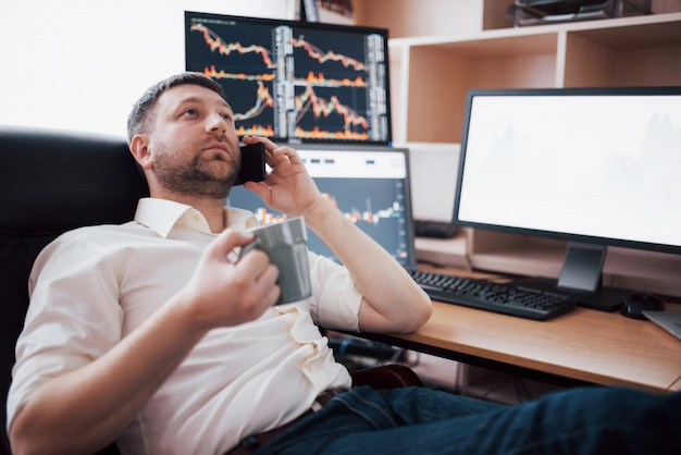 Vista por encima del hombro y negociación de corredores de bolsa en línea mientras acepta pedidos por teléfono. múltiples pantallas de computadora llenas de gráficos y análisis de datos en