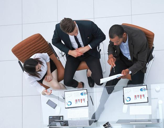 Vista desde el equipo empresarial superior discutiendo documentos financieros