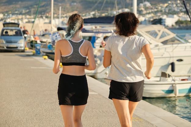 Vista de la espalda de madre e hija corriendo en el paseo marítimo