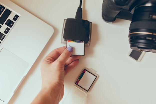 Vista desde el estudio de diseño de la mesa de trabajo, proceso de carga de imágenes desde su unidad flash en una computadora. cámara profesional rodeada, lentes, laptop, pendrives.