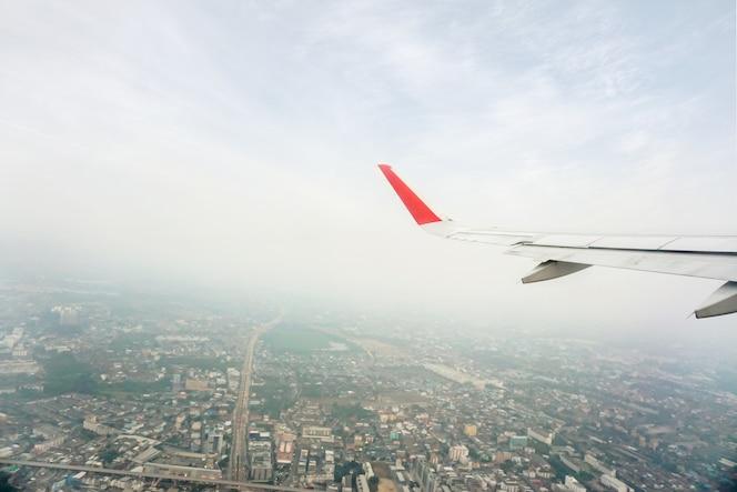 Vista exterior de la ventana del avión con ala de avión en el cielo azul