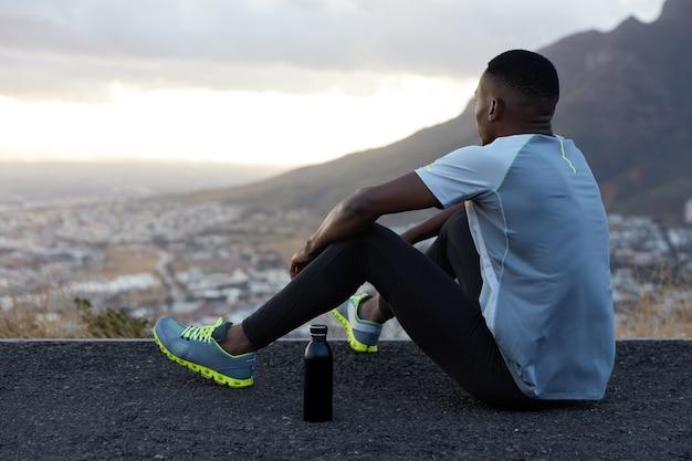 Vista exterior del relajado hombre afroamericano con piel oscura y saludable, bebe agua, se sienta en la colina, disfruta del hermoso paisaje, atmósfera tranquila, montañas, vestido con ropa deportiva. bienestar