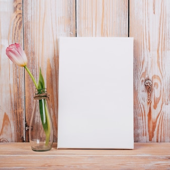 Vista de la flor del tulipán en el florero con cartel negro sobre fondo de madera