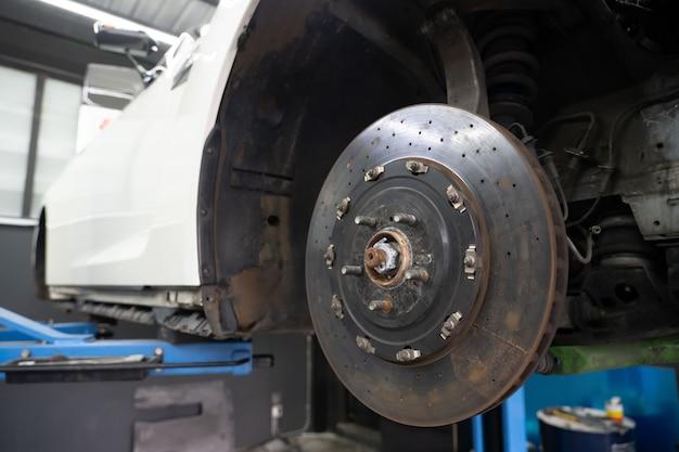 Vista del freno de disco del coche esperando para el reemplazo de neumáticos en el garaje