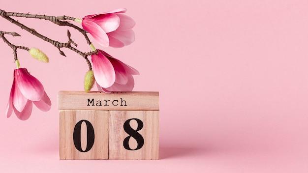 Vista frontal 8 de marzo letras con flores rosas y espacio de copia
