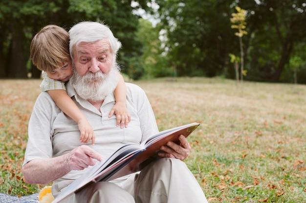 Vista frontal abuelo leyendo para nieto