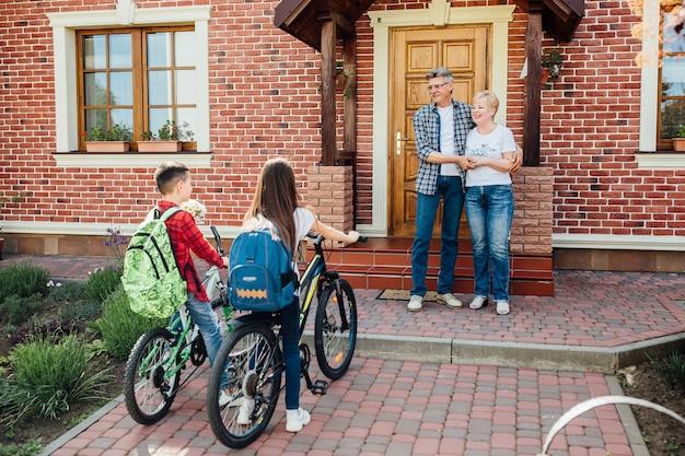 Vista frontal de los abuelos caucásicos de pie junto a la puerta e invitando a sus nietos a su casa.