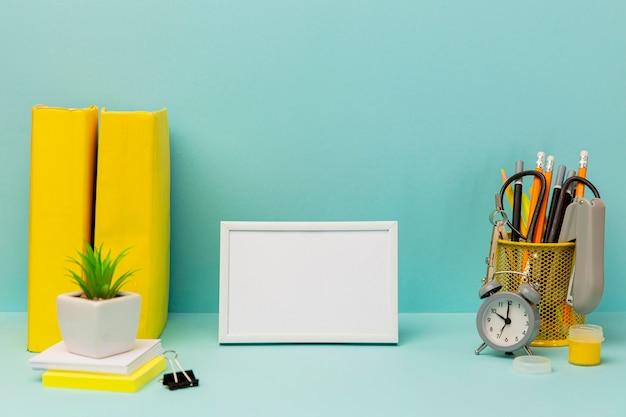 Vista frontal de accesorios de oficina con marco sobre la mesa