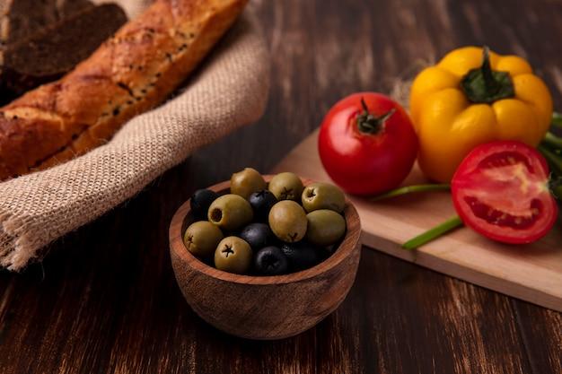 Vista frontal de aceitunas con tomates pimientos en una tabla y una hogaza de pan sobre un fondo de madera