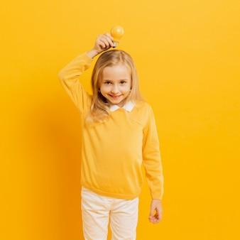Vista frontal de la adorable niña posando mientras sostiene la bombilla de luz amarilla