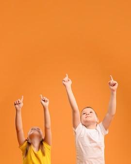 Vista frontal adorables niños apuntando hacia arriba
