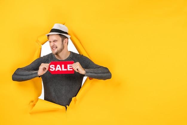 Vista frontal de un adulto joven divertido y emocional que muestra el cartel de venta en un rasgado en la pared amarilla