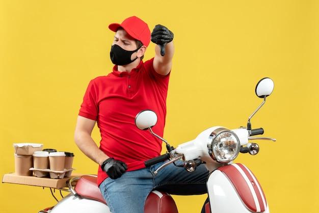 Vista frontal del adulto joven nervioso insatisfecho con blusa roja y guantes de sombrero en máscara médica entregando orden sentado en scooter apuntando hacia abajo sobre fondo amarillo