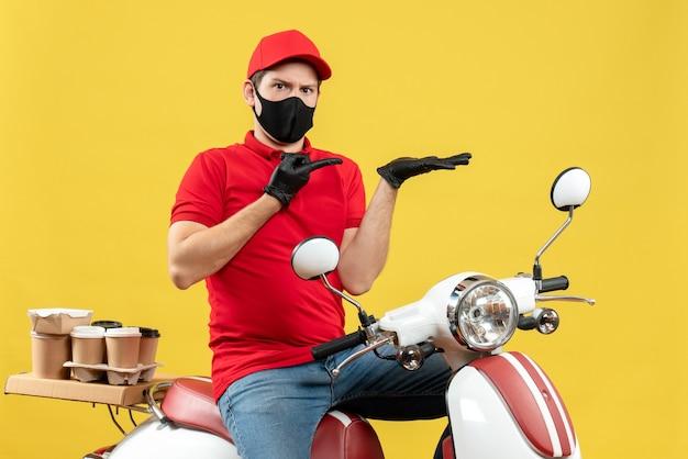 Vista frontal del adulto joven preguntándose vistiendo blusa roja y guantes de sombrero en máscara médica entregando orden sentado en scooter
