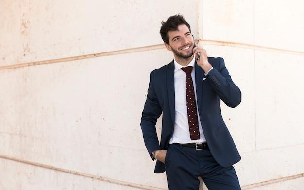 Vista frontal de adultos en traje hablando por teléfono