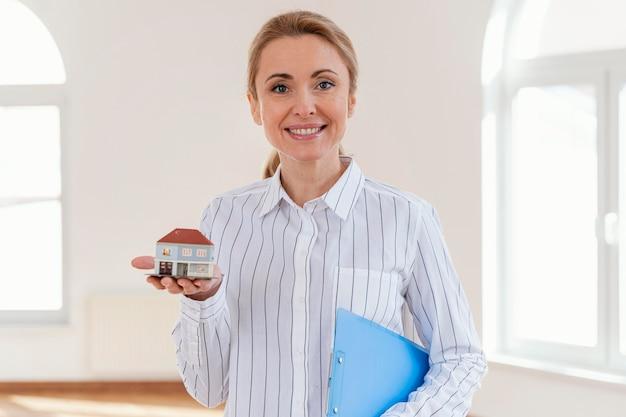Vista frontal del agente inmobiliario femenino sonriente con casa en miniatura