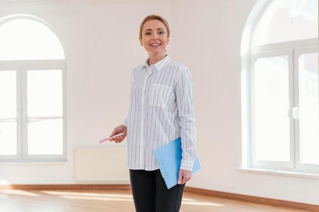 Vista frontal del agente inmobiliario femenino sonriente en casa vacía