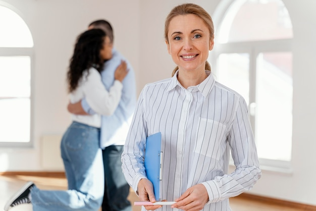 Vista frontal del agente inmobiliario femenino sonriente con la joven pareja abrazándose en el fondo
