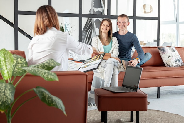 Vista frontal agente inmobiliario hablando con pareja
