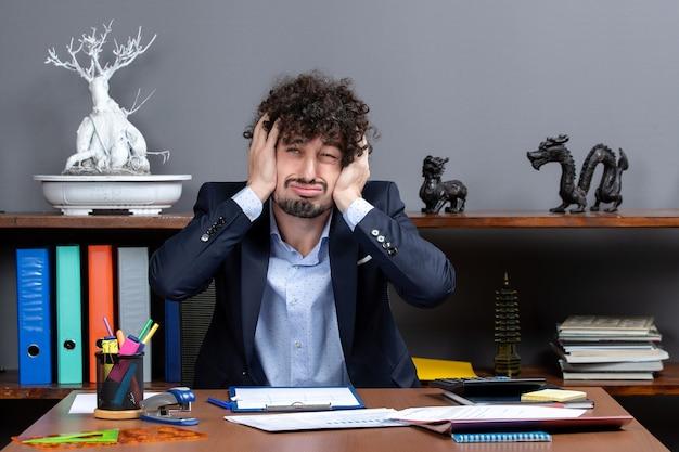 Vista frontal agitado empresario sentado en el escritorio holdinghis cabeza