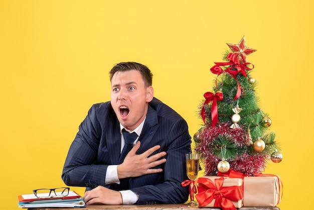 Vista frontal agitado joven sosteniendo su pecho sentado en la mesa cerca del árbol de navidad y presenta sobre fondo amarillo