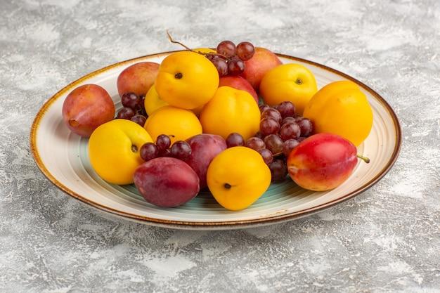 Vista frontal de albaricoques dulces frescos con ciruelas y uvas dentro de la placa en el escritorio blanco