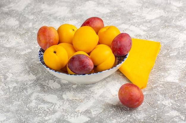 Vista frontal de albaricoques dulces frescos frutos amarillos dentro de la placa con ciruelas sobre superficie blanca