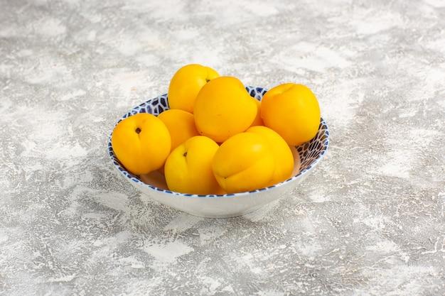 Vista frontal de albaricoques dulces frescos frutos amarillos dentro de la placa en la superficie blanca
