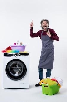Vista frontal alegre ama de llaves hombre apuntando al techo de pie cerca de la cesta de lavandería lavadora sobre fondo blanco.