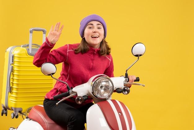 Vista frontal alegre joven en ciclomotor agitando la mano