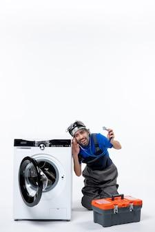 Vista frontal alegre reparador sosteniendo estetoscopio sentado cerca de la lavadora en el espacio en blanco