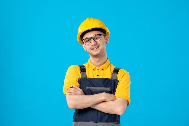 Vista frontal alegre trabajador masculino en uniforme amarillo sobre azul