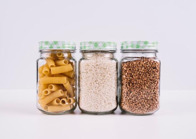 Vista frontal de alimentos en frascos sobre fondo blanco.