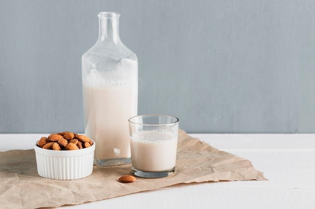Vista frontal de almendras con vaso y botella de leche
