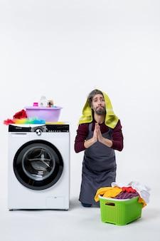 Vista frontal ama de llaves hombre de pie sobre la rodilla uniendo las manos canasta de lavandería sobre fondo blanco.