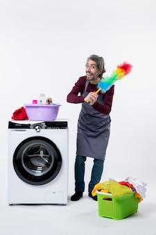 Vista frontal ama de llaves hombre sujetando plumero de pie cerca de la cesta de lavandería lavadora sobre fondo blanco.