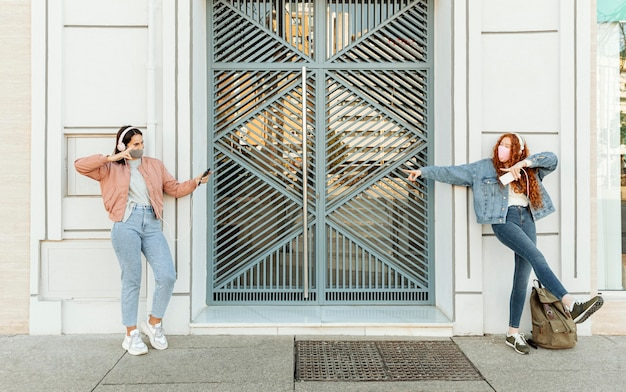 Vista frontal de amigas con máscaras faciales al aire libre usando teléfonos inteligentes y bailando