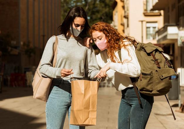 Vista frontal de amigas con mascarillas al aire libre con bolsa de compras