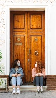 Vista frontal de amigas con mascarillas sentado junto a la puerta