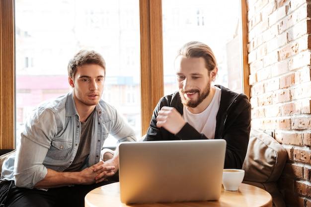 Vista frontal de amigos con laptop en café