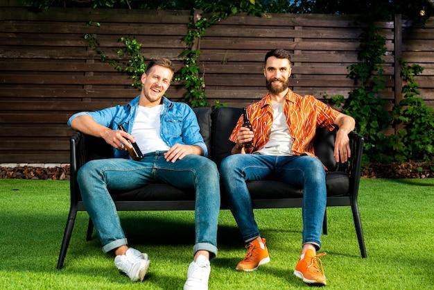 Vista frontal amigos sentados en un banco del jardín