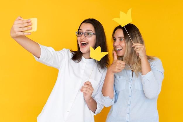 Vista frontal de amigos tomando selfies con corona
