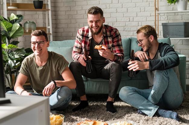Vista frontal de amigos varones sonrientes comiendo pizza y viendo deportes en la televisión con cerveza