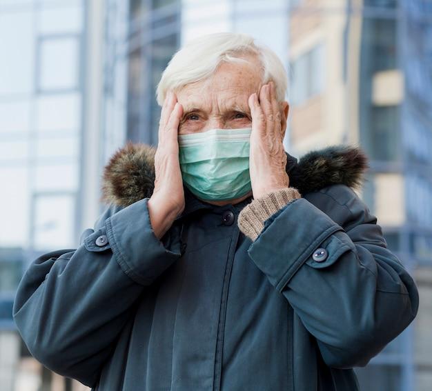 Vista frontal de la anciana con máscara médica mientras está en la ciudad