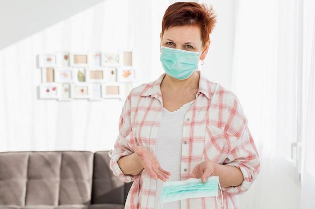Vista frontal de una anciana con máscara médica que muestra otra que está sosteniendo