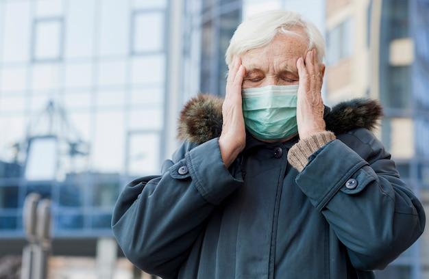Vista frontal de la anciana con máscara médica que no se siente bien mientras está afuera