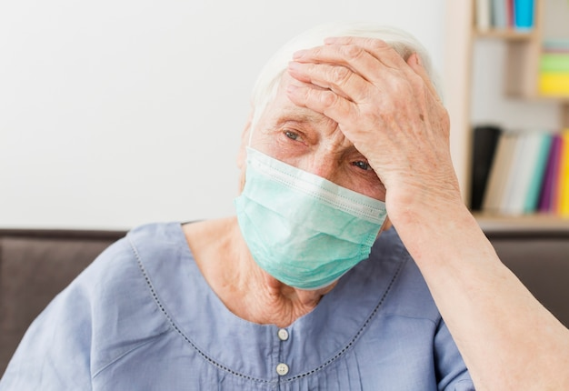 Vista frontal de la anciana con máscara médica sintiéndose enfermo