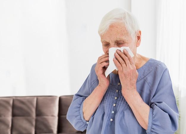 Vista frontal de la anciana sonarse la nariz en servilleta
